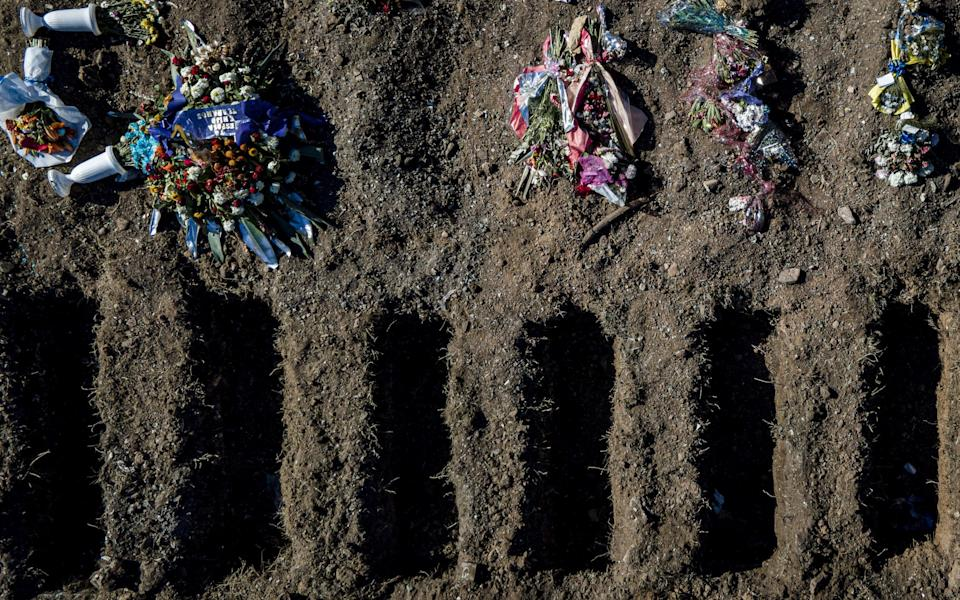Open graves and flowers laid by family members in the section destined for the victims of Covid-19 in the San Jose de Flores Cemetery in Buenos Aires, Argentina - Getty