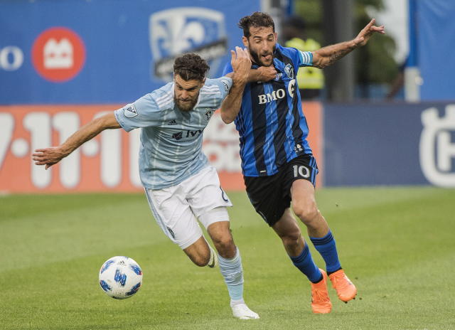 Montreal Impact's Ignacio Piatti, right, battles with Sporting Kansas City's Graham Zusi during the first half of an MLS soccer match Saturday, June 30, 2018, in Montreal. (Graham Hughes/The Canadian Press via AP)