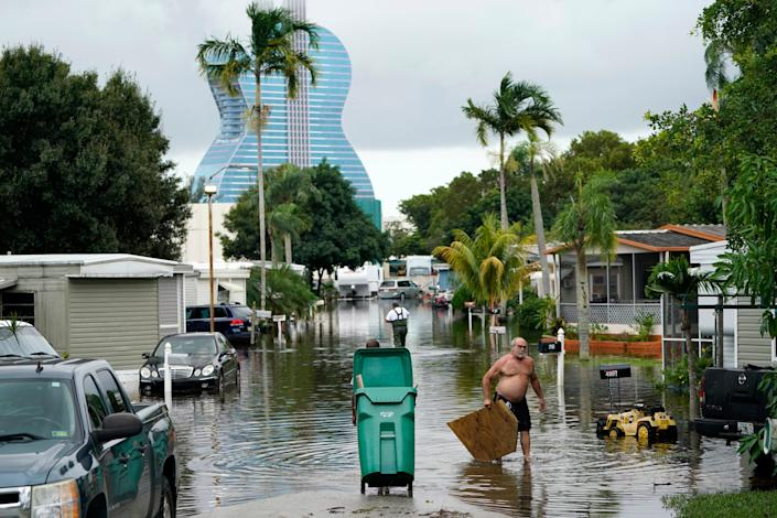 Residents clear debris from a flooded street in the Driftwood Acres Mobile Home Park in the shadow of the Guitar Hotel at Seminole Hard Rock, in the aftermath of Tropical Storm Eta on Tuesday (AP)