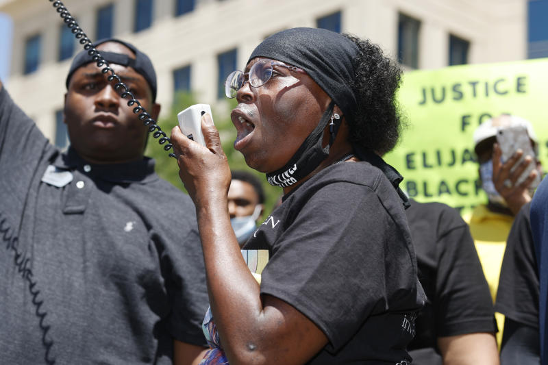 """FILE - In this June 27, 2020, file photo, Sheneen McClain speaks during a rally and march over the death of her 23-year-old son, Elijah McClain, outside the police department in Aurora, Colo. Multiple suburban Denver police officers have been placed on paid administrative leave amid an investigation into photos of them related to the case of a Black man who died last summer after he was stopped and restrained, police said Monday, June 29, 2020. The interim police chief of the city of Aurora, Vanessa Wilson, said in a statement that the suspended officers were """"depicted in photographs near the site where Elijah McClain died."""" But her statement did not provide more details about what the images show. (AP Photo/David Zalubowski, File)"""