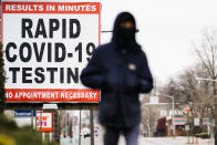 FILE - In this Jan. 25, 2021, file photo, a person wearing face mask as a precaution against the coronavirus walks near a sign advertising a rapid COVID-19 testing site in Philadelphia. U.S. healthy officials say that most fully vaccinated Americans can skip testing for COVID-19, even if they were exposed to someone infected. (AP Photo/Matt Rourke, File)