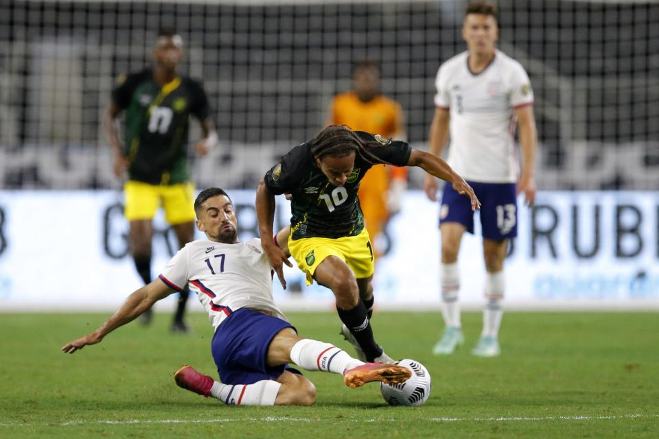 United States midfielder Sebastian Lletget (17) clears the ball away from Jamaica forward Bobby Reid (10) in the first half of a CONCACAF Gold Cup quarterfinals soccer match, Sunday, July 25, 2021, in Arlington, Texas. (AP Photo/Brandon Wade)