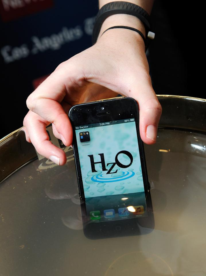 LAS VEGAS, NV - JANUARY 06:  An iPhone using HzO Waterblock technology is displayed in a bowl of water during a press event at the Mandalay Bay Convention Center for the 2013 International CES on January 6, 2013 in Las Vegas, Nevada. CES, the world's largest annual consumer technology trade show, runs from January 8-11 and is expected to feature 3,100 exhibitors showing off their latest products and services to about 150,000 attendees.  (Photo by David Becker/Getty Images)