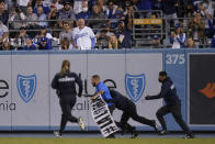 A fan who made his way on to the field is tackled by security personnel during a baseball game between the Arizona Diamondbacks and the Los Angeles Dodgers Wednesday, Sept. 15, 2021, in Los Angeles. (AP Photo/Ashley Landis)