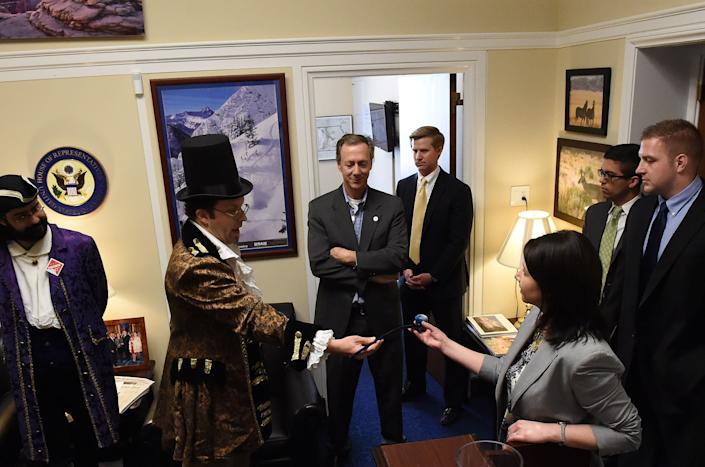 Dressed in colonial garb, Adam Eidinger and fellow D.C. marijuana advocates visit the office staff of Rep. Jason Chaffetz (R-Utah) at the Rayburn House Office Building on Capitol Hill on March 17, 2015, to protest the congressman's stand in regard to legalized marijuana in the District of Columbia. Legislative Director Amber Kirby Talley receives a pipe from Eidinger.