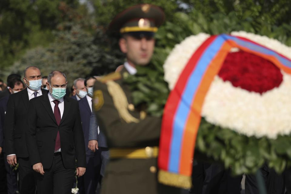 Armenian Prime Minister Nikol Pashinyan, second left, attends a memorial service at the monument to the victims of mass killings by Ottoman Turks, to commemorate the 106th anniversary of the massacre, in Yerevan, Armenia, Saturday, April 24, 2021. Armenians marked the anniversary of the death of up to 1.5 million Armenians by Ottoman Turks, an event widely viewed by scholars as genocide, though Turkey refutes the claim. (Tigran Mehrabyan/PAN Photo via AP)