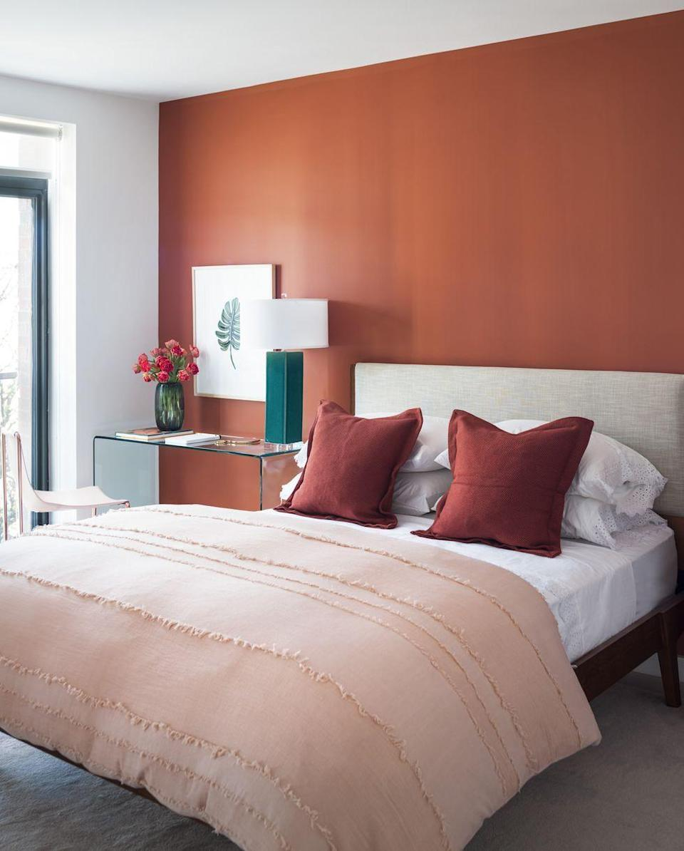 <p>A terracotta-colored accent wall and pillows warm up this bedroom, while soft peach and white tones offer just enough balance. <br></p>