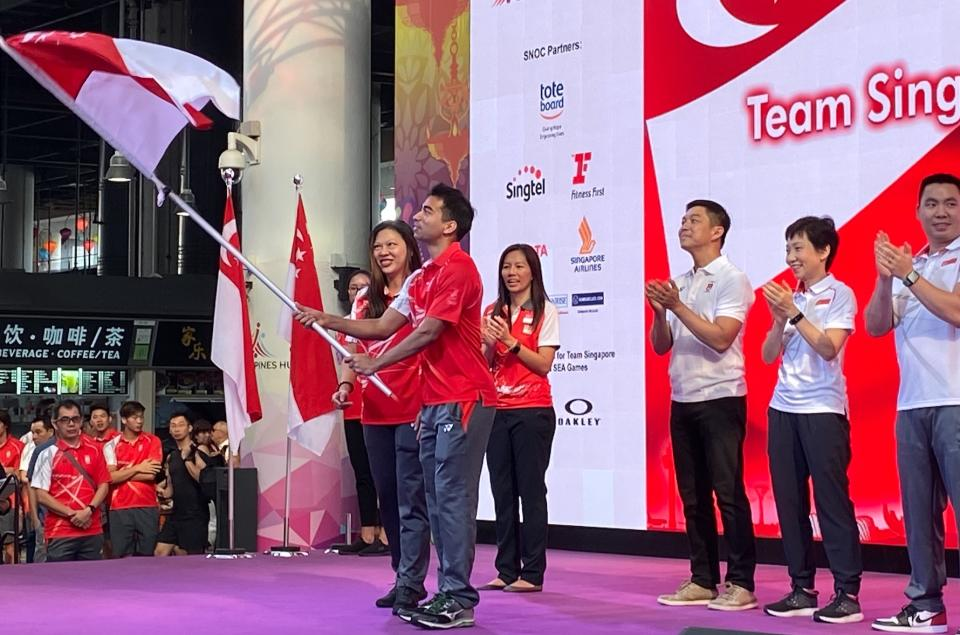 Squash player Samuel Kang, flag bearer for Team Singapore for the upcoming SEA Games, holds aloft the Singapore flag at the flag presentation ceremony at Our Tampines Hub. (PHOTO: Chia Han Keong/Yahoo News Singapore)