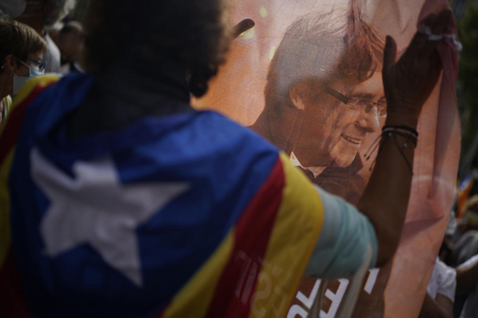 A man holds printed image of former Catalan leader Carles Puigdemont as people take part in a protest outside the Italian consulate in support of Puigdemont in Barcelona, Spain, Friday, Sept. 24, 2021. Puigdemont, who fled Spain after a failed secession bid for the northeastern region in 2017, was detained Thursday in Sardinia, Italy, his lawyer said. Puigdemont, who lives in Belgium and now holds a seat in the European Parliament, has been fighting extradition to Spain, which accused him and other Catalan independence leaders of sedition. (AP Photo/Joan Mateu)