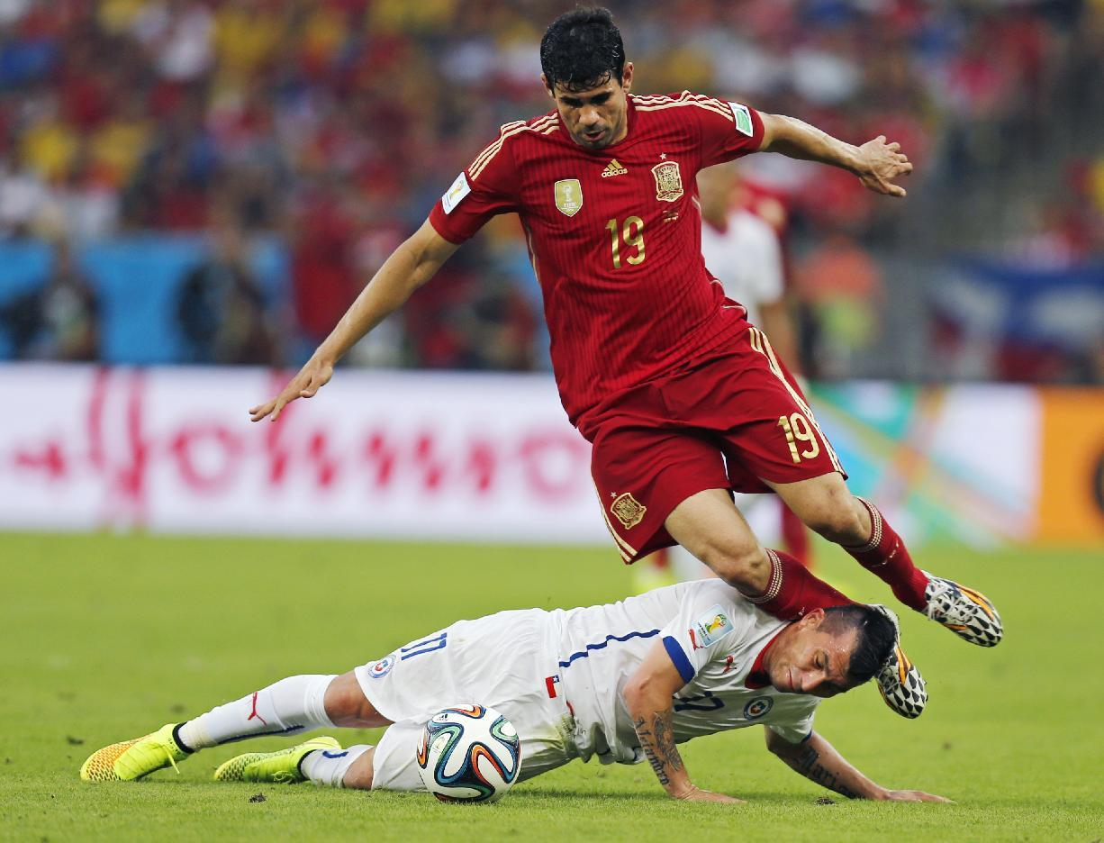 Spain's Diego Costa trips over Chile's Gary Medel during the group B World Cup soccer match between Spain and Chile at the Maracana Stadium in Rio de Janeiro, Brazil, Wednesday, June 18, 2014.  (AP Photo/Frank Augstein)