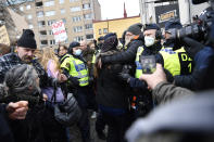 Anti-lockdown protesters face police as they demonstrate against coronavirus restrictions in Stockholm Saturday March 6, 2021. The protest was disbanded by police due to lack of permit for the public gathering. (Henrik Montgomery / TT via AP)