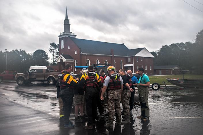 Rescue crews from Robeson County and the Cajun Navy go over maps in the parking lot of the Sandy Grove Baptist Church before launching their boats into a neighborhood on the south side of Lumberton on Sunday.