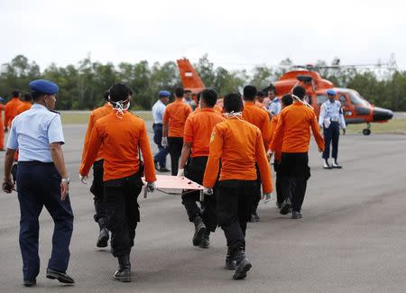 Indonesian Search and Rescue crews prepare to receive recovered bodies of AirAsia passengers recovered from the sea at the airport in Pangkalan Bun, central Kalimantan December 31, 2014. REUTERS/Darren Whiteside