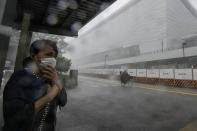 A woman takes shelter under a bus stop as heavy rain and hail come down outside Ariake Arena, where Olympic volleyball will be held, Sunday, July 11, 2021, in Tokyo. The fourth state of emergency would go in effect on Monday and last through Aug. 22, despite the opening ceremony of Tokyo Olympics that's scheduled to be held in less than two weeks. (AP Photo/Kiichiro Sato)