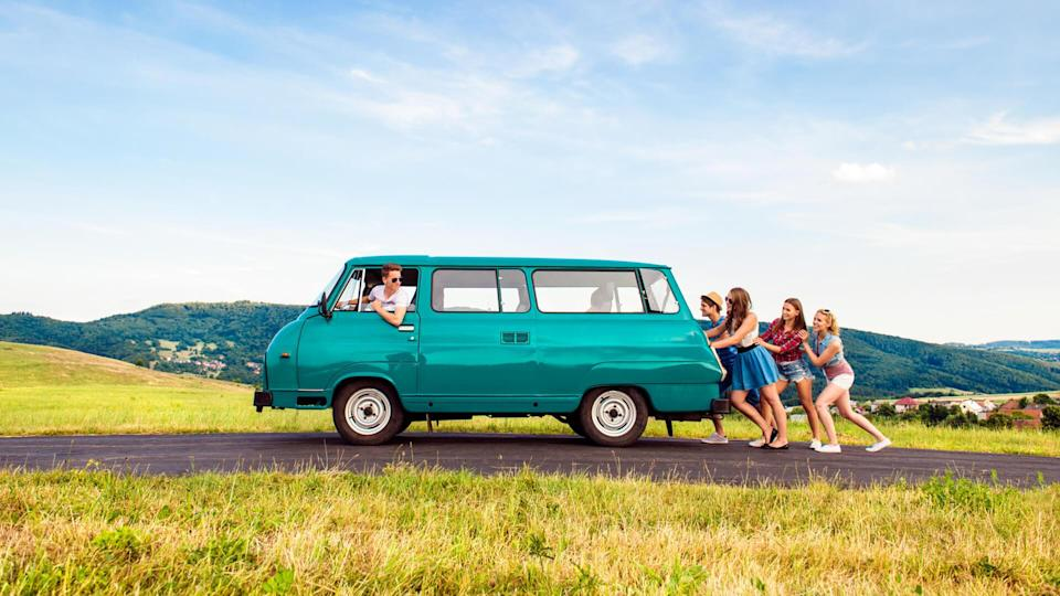 Young teenage hipster frieds with campervan against green nature and blue sky, jumping.