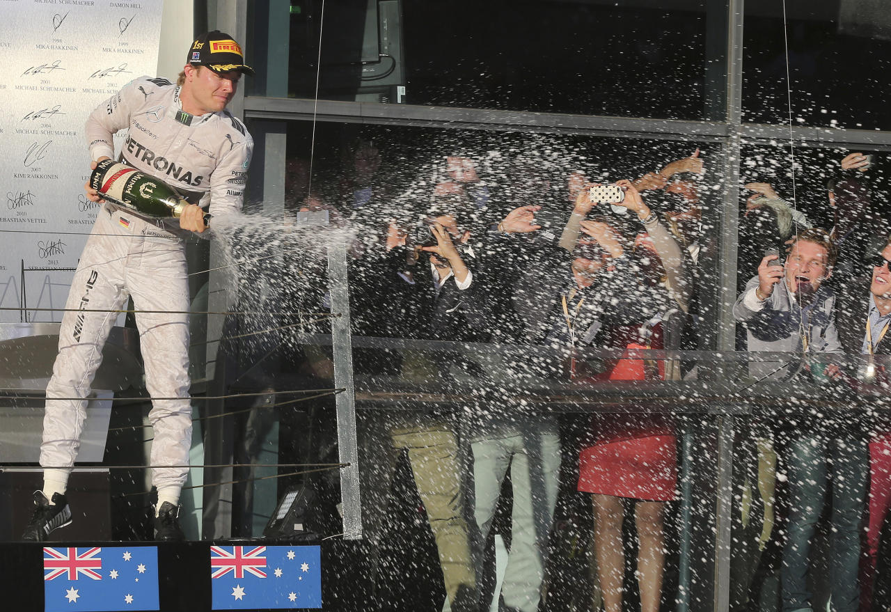 Mercedes driver Nico Rosberg of Germany sprays champagne in celebration after winning the Australian Formula One Grand Prix at Albert Park in Melbourne, Australia, Sunday, March 16, 2014. (AP Photo/Rob Griffith)