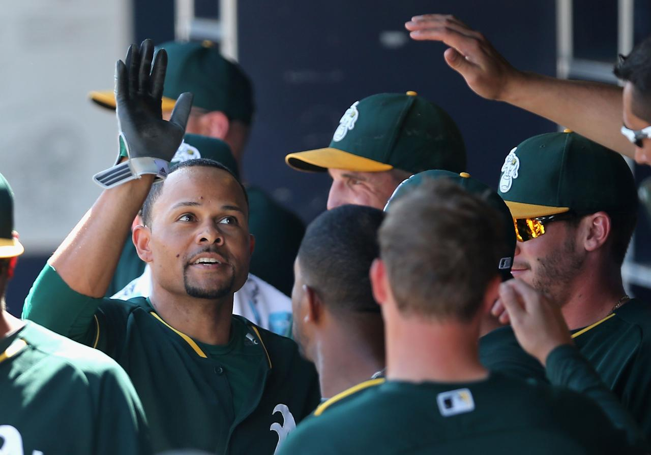 PEORIA, AZ - MARCH 11:  Coco Crisp #4 of the Oakland Athletics high fives teammates in the dugout after scoring a first inning run against the San Diego Padres during the spring training game at Peoria Stadium on March 11, 2014 in Peoria, Arizona.  (Photo by Christian Petersen/Getty Images)