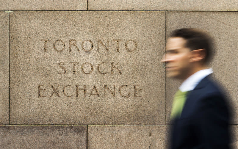 A man walks past an old Toronto Stock Exchange sign in Toronto