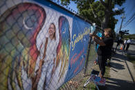 CORRECTS TO FUNERAL HOME VIEWING INSTEAD OF FUNERAL A woman places a decoration near a poster after attending the funeral home viewing of Gabby Petito at Moloney's Funeral Home in Holbrook, N.Y. Sunday, Sept. 26, 2021. (AP Photo/Eduardo Munoz Alvarez)