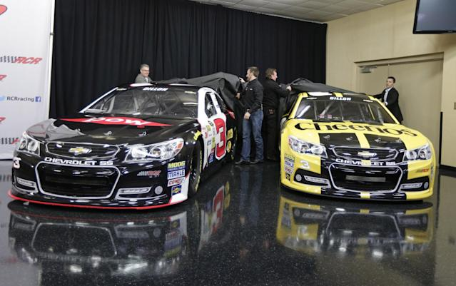 Austin Dillon, center left, and team owner Richard Childress, center right, help unveil the cars Dillon will drive in the 2014 NASCAR Sprint Cup series during a news conference at Charlotte Motor Speedway in Concord, N.C., Wednesday, Dec. 11, 2013. The late Dale Earnhardt's famed No. 3 will be back on track in the elite Sprint Cup Series next season with Dillon using the number. (AP Photo/Chuck Burton)