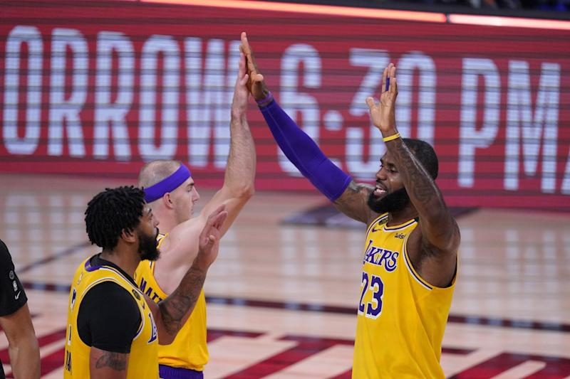 Lakers teammates Anthony Davis, Alex Caruso and LeBron James celebrate during the final minute.