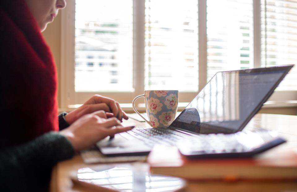A woman using a laptop on a dining room table set up as a remote office to work from home