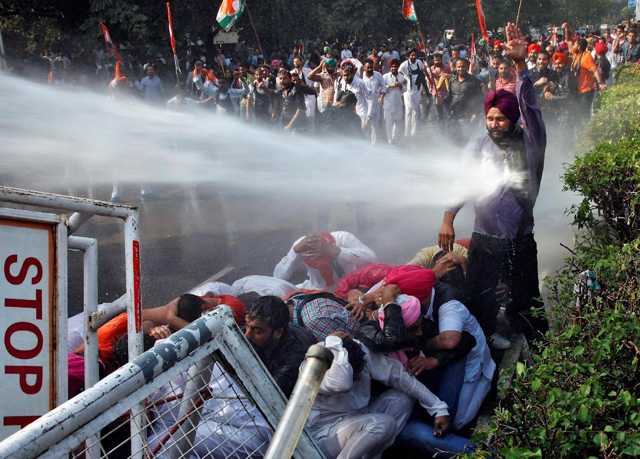 A demonstrator is hit by a water cannon used by police to disperse the protestors during a protest against what they say is state government's failure to arrest those involved in the sacrilege of Guru Granth Sahib, the religious book of Sikhs, in Behbal Kalan village of Punjab in 2015, in Chandigarh, India October 26, 2016. REUTERS/Ajay Verma