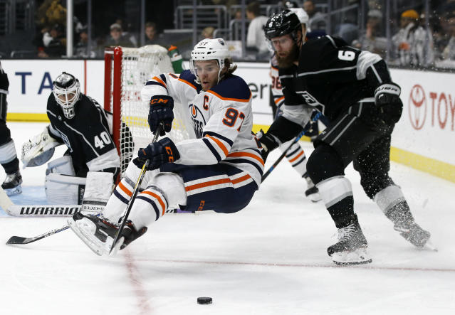 Edmonton Oilers center Connor McDavid, center, loses an edge to fall to the ice with Los Angeles Kings defenseman Jake Muzzin, right, defending with goaltender Calvin Petersen, left, during the third period of an NHL hockey game in Los Angeles, Sunday, Nov. 25, 2018. Kings won 5-2. (AP Photo/Alex Gallardo)