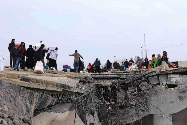 PHOTO: This photo provided on Jan. 30, 2020, shows displaced Syrians fleeing the Syrian military offensive in Idlib province, walking over a destroyed bridge as they arrive in Manbij, north Syria. (Northern Democratic Brigade via AP)