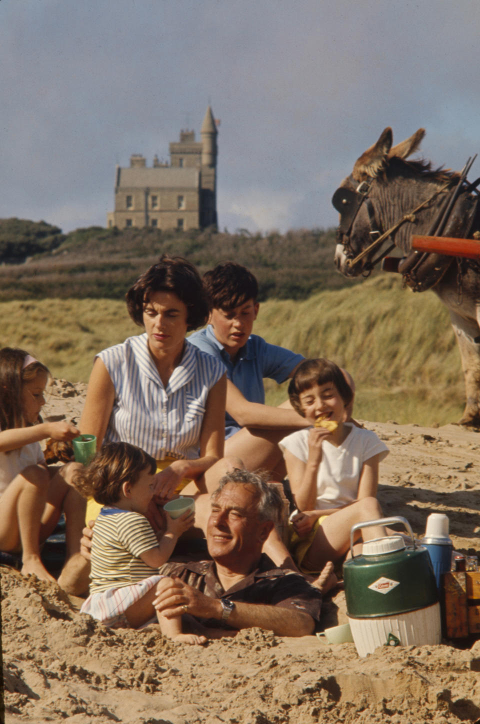 At the beach in front of Classiebawn Castle, Louis Mountbatten, 1st Earl Mountbatten of Burma (1900 - 1979) (center, buried in sand) plays his daughter, Lady Patricia Bradbourne (later 2nd Countess Mountbatten of Burma), and her children, from left, Joanna, Philip, Norton (later Lord Brabourne, in back), and Amanda, County Sligo, Ireland, 1963. (Photo by Ralph Crane/The LIFE Picture Collection via Getty Images)