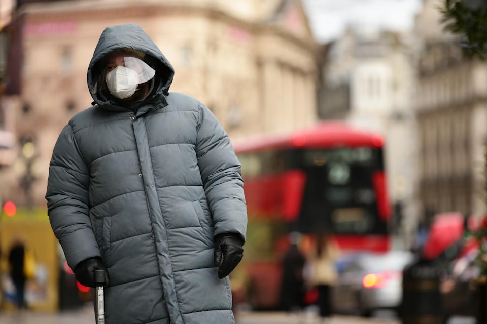 A man wearing a face mask and face shield waits at a pedestrian crossing on Regent Street in London, England, on December 21, 2020. London spent its second day of what could be months under newly-introduced 'Tier 4' coronavirus restrictions today. Under Tier 4 rules non-essential shops and many other businesses including gyms and hairdressers must close, with people instructed to stay at home other than for exempted circumstances including travel to work or education. Indoor mixing between those in different households is also banned under the new tier, upending Christmas plans for a huge swathe of the population. Concern over a more infectious strain of the coronavirus in the UK has meanwhile seen dozens of countries ban arrivals from Britain, with food supplies also disrupted after France closed the cross-Channel freight route from Dover. (Photo by David Cliff/NurPhoto via Getty Images)