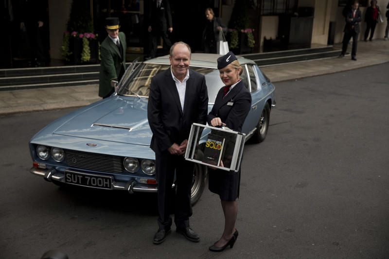 """William Boyd, the author of the new James Bond novel """"Solo"""" poses for photographers with a flight attendant during a launch photocall outside the Dorchester Hotel in London, Wednesday, Sept. 25, 2013. """"Solo"""" is set in 1969 and takes the suave British spy, 45 years old and feeling his age, from London's plush Dorchester Hotel to a war-torn West African country and to Washington. (AP Photo/Matt Dunham)"""