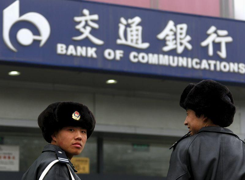 File photo of security guards standing outside a branch of the Bank of Communications located in central Beijing
