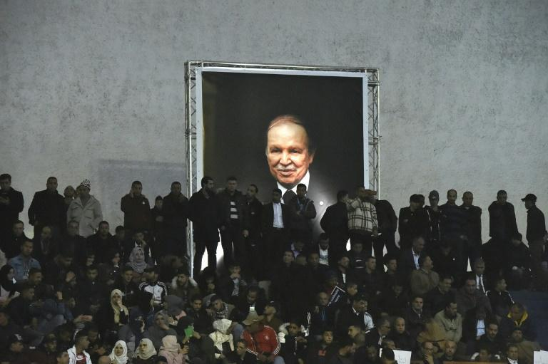 Supporters of Algeria's National Liberation Front (FLN) party gather on February 9, 2019 in the capital Algiers to call upon President Abdelaziz Bouteflika (shown in a poster) to run for a fifth term -- his decision to stand sparked mass protests (AFP/RYAD KRAMDI)