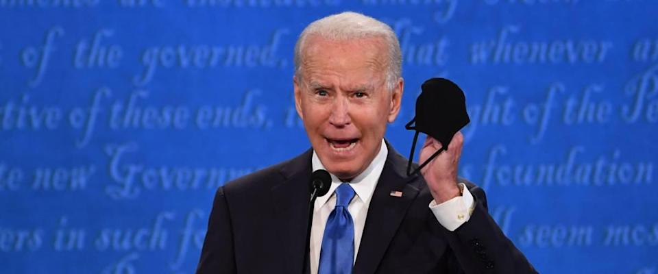 Joe Biden at presidential debate talking into microphone holding his face mask in his hand