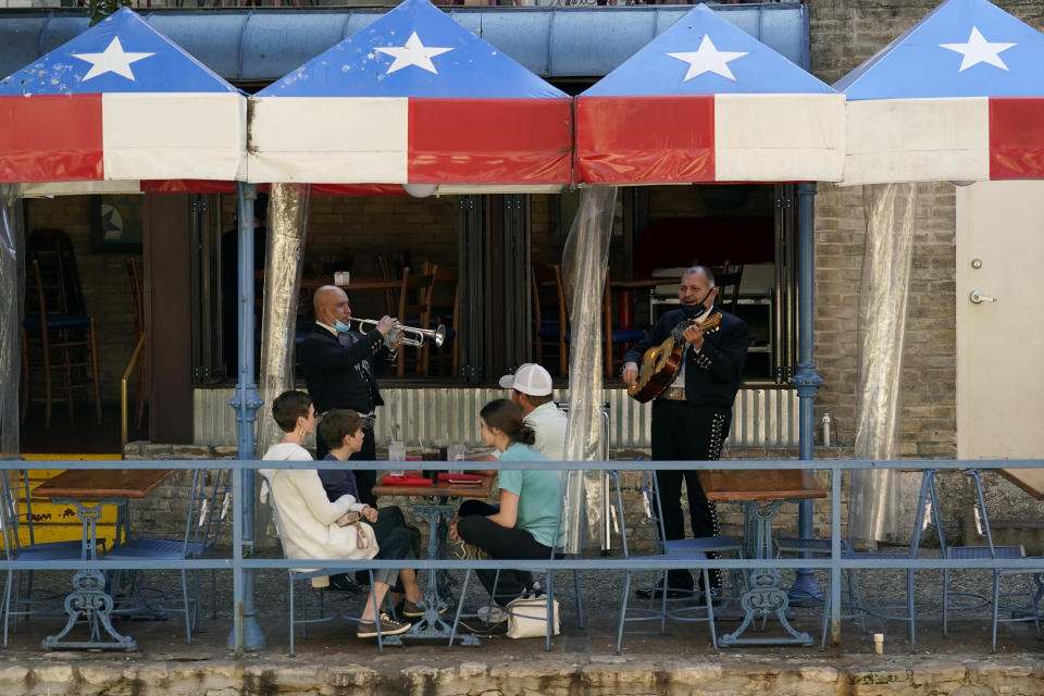 FILE - In this March 3, 2021, file photo, mariachi perform for diners at a restaurant on the River Walk in San Antonio. U.S. employers added a surprisingly robust 379,000 jobs in February in a sign the economy is strengthening as virus cases drop, vaccinations ramp up, Americans spend more and states ease business restrictions. Texas joined some other states in announcing it will fully reopen its economy. (AP Photo/Eric Gay, File)