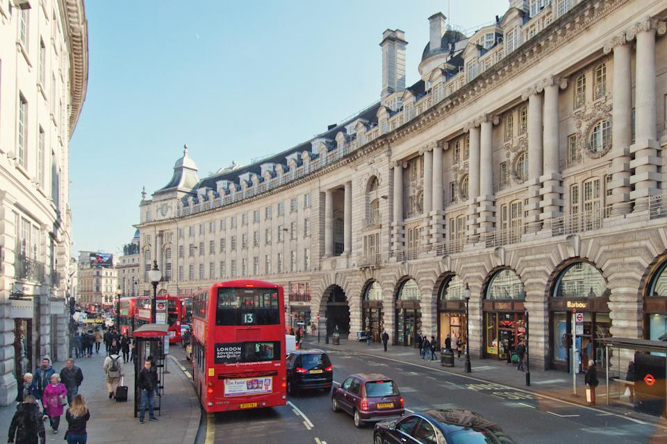 People walking and shopping on the sidewalks of the major shopping street of Regent Street in London.