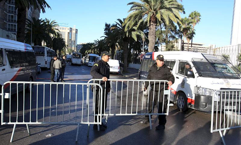 Tunisian policemen stand near a presidential guard bus at the scene of a suicide bomb attack in Tunis