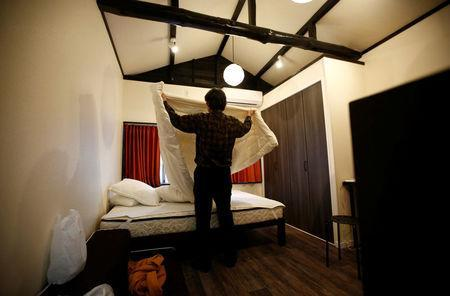 Yasuhiro Inaoka, who manages apartments for owners who provide short-term homestay lodging, arranges a bed after guests checked out at an apartment which is used as Airbnb service in Tokyo, Japan March 12, 2018. REUTERS/Kim Kyung-Hoon
