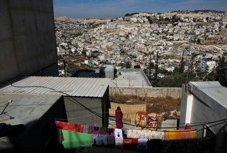 FILE PHOTO: A woman hangs laundry outside her house in the East Jerusalem neighbourhood of Jabal Mukaber November 23, 2010. Jerusalem's Old City (top L) and the East Jerusalem neighbourhoods of Ras al-Amud (R) and Silwan (L) are seen in the background. REUTERS/Ronen Zvulun/File Photo