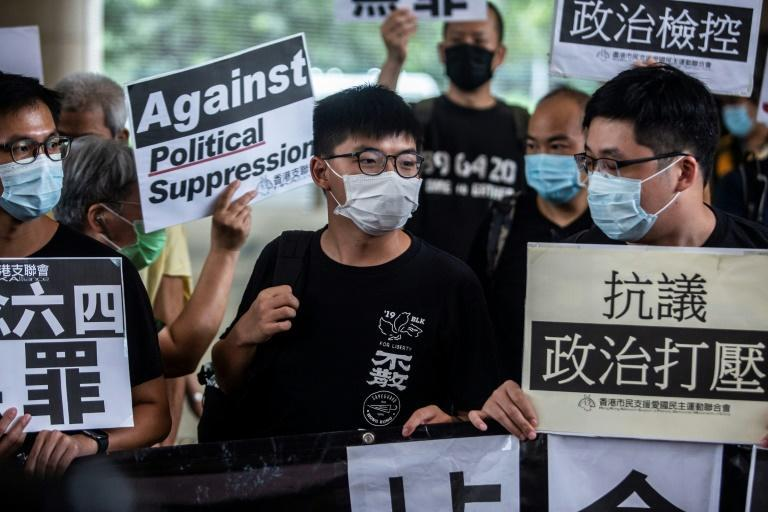 Pro-democracy activist Joshua Wong (C) is currently serving a jail sentence for taking part in a protest during the months of huge and often violent democracy rallies that rocked Hong Kong in 2019