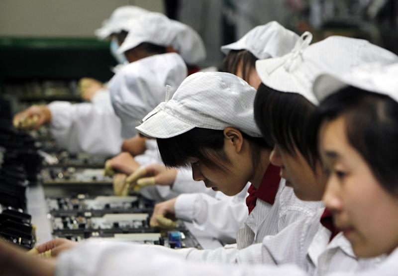 FILE-In this Wednesday, May 26, 2010, file photo, staff members work on the production line at the Foxconn complex in Shenzhen, China. Foxconn, the company that makes Apple's iPhones suspended production at a factory in China on Monday, Sept. 24, 2012, after a brawl by as many as 2,000 employees at a dormitory injured 40 people. The fight, the cause of which was under investigation, erupted Sunday night at a privately managed dormitory near a Foxconn Technology Group factory in the northern city of Taiyuan, the company and Chinese police said.(AP Photo/Kin Cheung, File)
