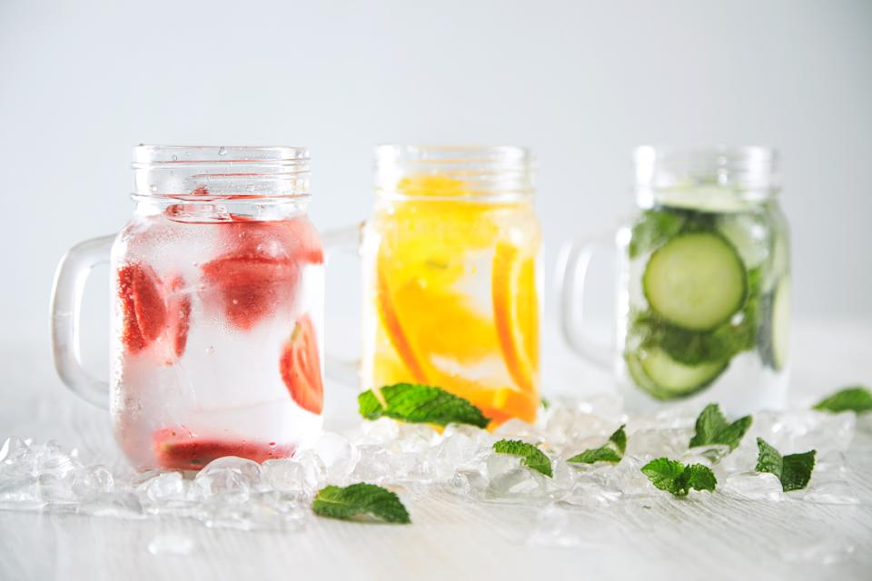 Close focus on first jar Healthy fresh cool homemade lemonades with sparkling water strawberry, cucumber,mint and orange isolated in smashed ice cubes on wooden table