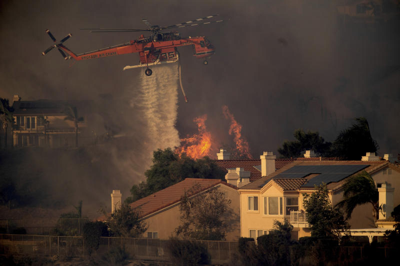 FILE - In this Oct. 11, 2019, file photo, a helicopter drops water while battling a wildfire called the Saddle Ridge Fire in Porter Ranch, Calif. Fire officials say a destructive fire that broke out on the edge of Los Angeles began beneath a high-voltage transmission tower. The destructive fire that broke out on the edge of Los Angeles began beneath a high-voltage transmission tower owned by Southern California Edison, fire officials said Monday, Oct. 14, 2019. (AP Photo/Noah Berger, File)