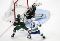 Minnesota Wild goalie Alex Stalock (32) makes a save as teammate Jared Spurgeon (46) and Vancouver Canucks' Antoine Roussel (26) go for the rebound during second-period NHL hockey game action in Edmonton, Alberta, Thursday, Aug. 6, 2020. (Jason Franson/The Canadian Press via AP)