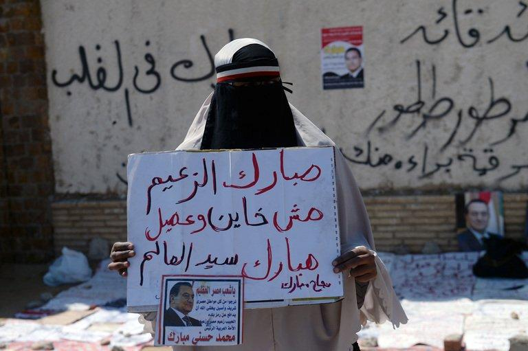 An Egyptian supporter of Egypt's ousted president Hosni Mubarak holds a placard during a demonstration outside the Police Academy in Cairo during his retrial on April 13, 2013. Mubarak appeared in court on Saturday to face a new trial for complicity in the murder of hundreds protesters during the 2011 uprising, as well as for corruption