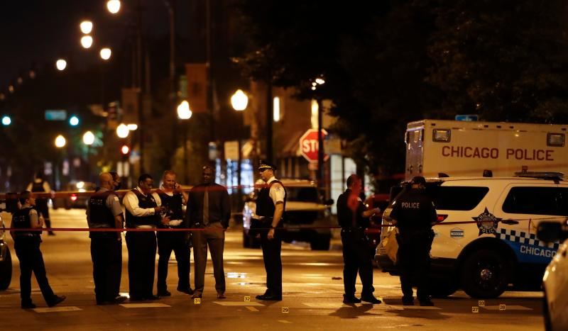 Chicago Police officers investigate the scene of a shooting in Chicago, Illinois, on July 21, 2020. - A shootout outside a funeral left 14 people wounded July 21 in Chicago, as President Donald Trump threatens to send federal agents to a handful of US cities led by Democratic mayors. (Photo by KAMIL KRZACZYNSKI / AFP) (Photo by KAMIL KRZACZYNSKI/AFP via Getty Images)