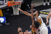 Utah Jazz center Rudy Gobert, above right, dunks as Golden State Warriors' Stephen Curry, left, and James Wiseman (33) defend during the first half of an NBA basketball game Saturday, Jan. 23, 2021, in Salt Lake City. (AP Photo/Rick Bowmer)