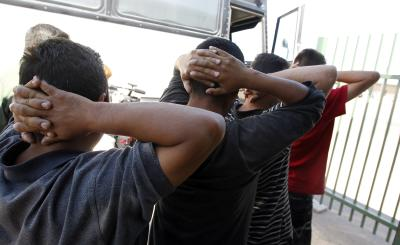 In this Aug. 9, 2012 file photo, newly arrived people who were caught in Arizona by the U.S. Border Patrol, are initially processed at Tucson Sector U.S. Border Patrol Headquarters in Tucson, Ariz. A major U.S. effort to discourage repeated attempts by immigrants to enter the country illegally by flying and busing them into Mexico hundreds of miles away from where they were caught has been sharply scaled back after producing relatively modest gains. (AP Photo/Ross D. Franklin, file)