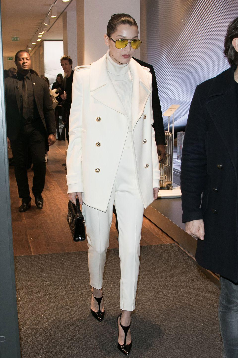 <p>In a white turtleneck and straight-legged trouser with a matching peacoat, black pointed-toe heels and yellow aviator sunglasses while out in Paris.</p>